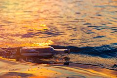 Message in a corked bottle on shore, hope of salvation stock photography