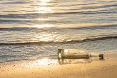 Message in a corked bottle on shore, hope of salvation royalty free stock image