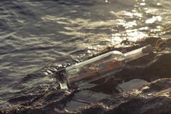 Message in a corked bottle on shore, hope of salvation royalty free stock photos