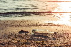 Message in a corked bottle on shore, hope of salvation. Message in a corked bottle on the shore, hope of salvation royalty free stock photography