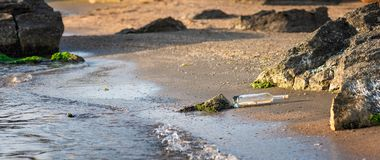 Message in a corked bottle on shore, hope of salvation. Message in a corked bottle on the shore, hope of salvation royalty free stock photo