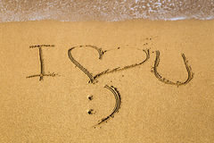 Message d'amour écrit en sable Images stock