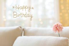 Message d'anniversaire avec la fleur dans le sofa intérieur de pièce photos stock