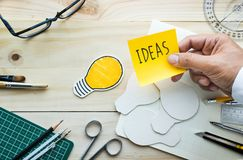Message d'idées sur le bloc-notes avec la main masculine sur la table de travail photo stock