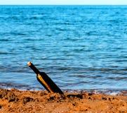 Message dans la bouteille en verre dans l'océan Photos stock