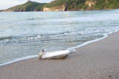 Message dans la bouteille lavée vers le haut du littoral isolé Photos libres de droits