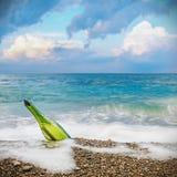 Message dans la bouteille sur la plage photographie stock