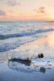 Message dans une bouteille au coucher du soleil Images libres de droits