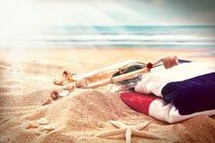 Message dans une bouteille avec la serviette de plage Images stock