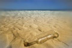 Message dans une bouteille dans le sable de la plage photo libre de droits