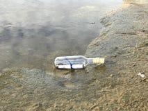 Message dans une bouteille en cristal dans la plage avec l'eau et le sable Photographie stock libre de droits