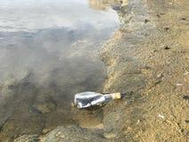 Message dans une bouteille en cristal dans la plage avec l'eau et le sable Photos libres de droits