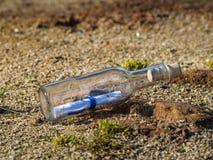 Message dans une bouteille en cristal dans la plage avec l'eau et le sable Photographie stock