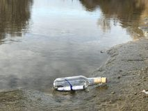 Message dans une bouteille en cristal dans la plage avec l'eau et le sable Images stock
