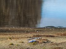 Message dans une bouteille en cristal dans la plage avec l'eau et le sable Image stock