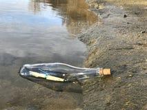 Message dans une bouteille en cristal dans la plage avec l'eau et le sable Photo libre de droits