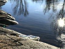 Message dans une bouteille en cristal dans la plage avec la réflexion de l'eau et de sable et de soleil sur l'eau Photo libre de droits