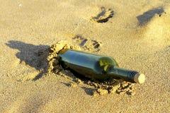 Message dans une bouteille en verre dans une plage Photos libres de droits