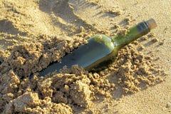 Message dans une bouteille en verre dans une plage Photo stock