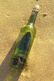 Message dans une bouteille en verre dans une plage Images stock