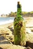 Message dans une bouteille en verre dans une plage Photos stock