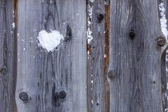 Message de aimé avec un symbole sous forme de coeur façonné de la neige sur une barrière en bois la Saint-Valentin photo libre de droits