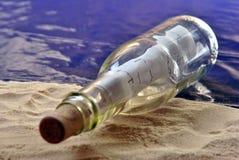 Message de bouteille sur une plage sablonneuse Image stock