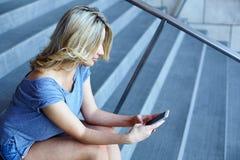 Message de dactylographie de fille au téléphone portable et se reposer sur des escaliers photographie stock