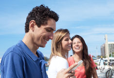 Message de dactylographie de type mexicain au téléphone avec des amies à l'arrière-plan Photographie stock libre de droits