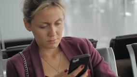 Message de dactylographie femelle caucasien attrayant sur le smartphone tout en se reposant sur le terminal d'aéroport Réfléchi e banque de vidéos