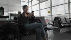 Message de dactylographie femelle caucasien attrayant sur le smartphone tout en se reposant sur le terminal d'a?roport Ulba et he clips vidéos