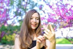Message de dactylographie de fille avec du charme sur le smatrphone avec le fond de fleur Image stock