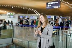 Message de dactylographie de gentille femme par le smartphone à l'aéroport, manteau de port Image libre de droits