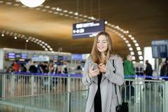Message de dactylographie de jeune femme caucasienne par le smartphone à l'aéroport, manteau de port Photographie stock
