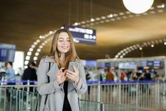 Message de dactylographie de jeune femme européenne par le smartphone à l'aéroport, manteau de port Images libres de droits