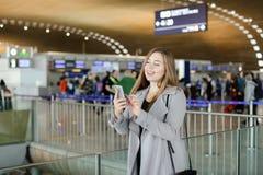 Message de dactylographie de jeune femme par le smartphone à l'aéroport, manteau de port Photographie stock libre de droits