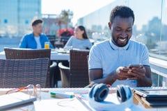 Message de dactylographie de jeune homme attirant au téléphone Photographie stock libre de droits