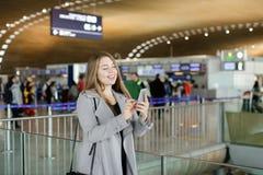 Message de dactylographie de jolie femme par le smartphone à l'aéroport, manteau de port Photos stock