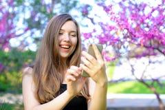 Message de dactylographie de personne féminine sur le smatrphone avec le fond de fleur Photo stock