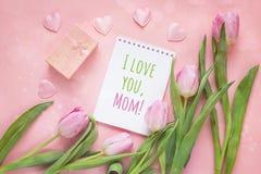 Message de jour de mères avec le bloc-notes, les tulipes et le boîte-cadeau sur un rose Image stock