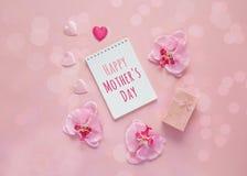 Message de jour de mères avec le boîte-cadeau, les fleurs d'orchidée et les coeurs dessus Photo libre de droits