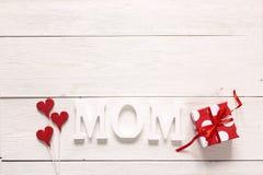 Message de jour de mères avec le boîte-cadeau rouge et coeurs décoratifs sur W Photographie stock libre de droits