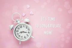 Message de jour de mères avec le réveil d'amour sur un fond rose Image libre de droits
