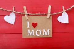 Message de jour de mères avec des pinces à linge au-dessus de conseil en bois rouge Images libres de droits