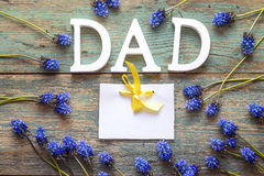 Message de jour de pères avec la carte de papier blanc et fleurs bleues sur o Photo stock
