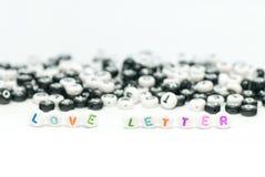 Message de lettre d'amour écrit avec les lettres colorées et la lettre noire et blanche à l'arrière-plan sur la photo blanche de  Photos libres de droits