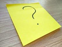 Message de point d'interrogation sur la note collante jaune sur le fond en bois photo libre de droits