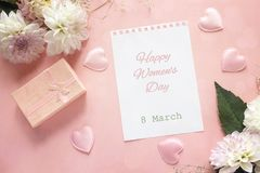 Message de salutation de jour du ` s de femmes avec les dahlias et le boîte-cadeau sur le rose photographie stock libre de droits