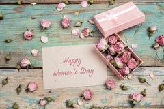 Message de salutation de jour du ` s de femmes avec de petites roses roses dans une boîte dessus image stock