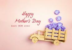 Message de salutation de jour de mères avec le camion en bois de jouet avec f violet photographie stock